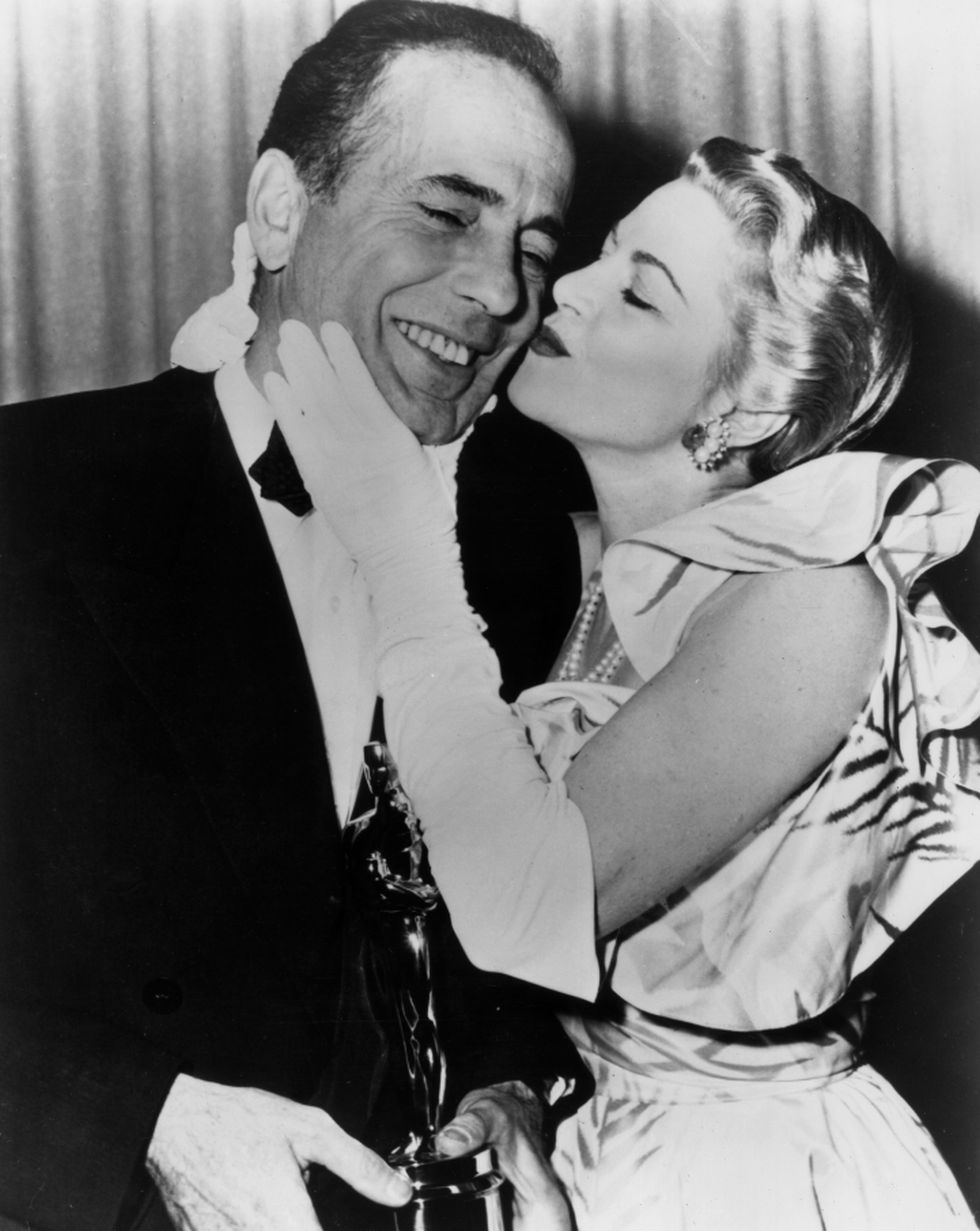 El actor Humphrey Bogart recibe un beso de su colega Claire Trevor en el backstage de los Óscar 1952 (Getty Images)